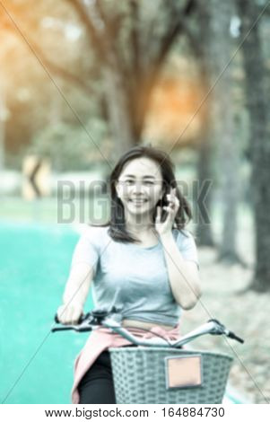 de-focused Attractive woman taking with phone while ride bicycle in countryside road lifestyle concept cool tone