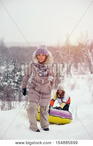 Two female friends having fun on snow hill. People sledding on snow tubings. Winter vacation.