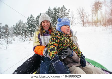 Two women and little child hugging and laughing on snow tubing. Group of caucasian adults and kid having fun outdoors. Winter vacation.