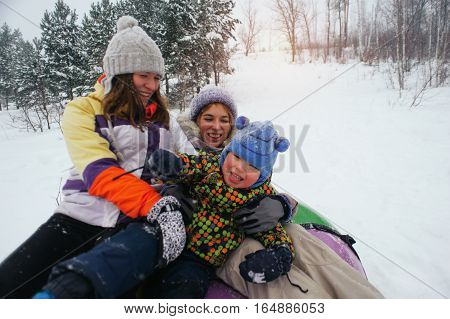 Group of caucasian women and child having fun on snow. People sitting on tube and laughing. Winter vacation
