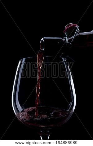 Red Wine Pouring Into A Wineglass. Isolated On Black Background.