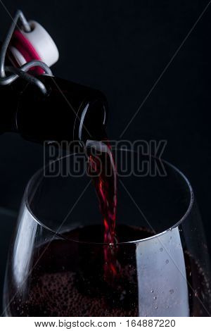 Close Up Of Red Wine Pouring In Glass.