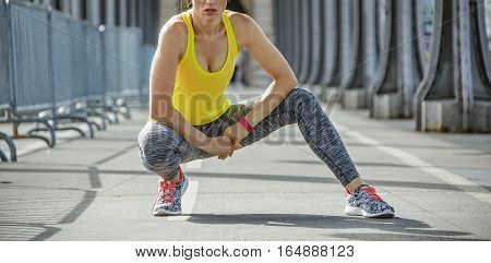 Outdoors fitness in Paris. young healthy woman relaxing after workout on Pont de Bir-Hakeim bridge in Paris