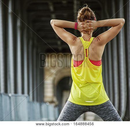Outdoors fitness in Paris. Seen from behind young sportswoman stretching on Pont de Bir-Hakeim bridge in Paris