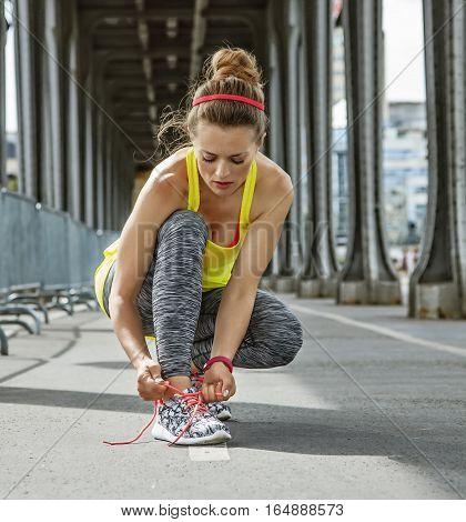 Outdoors fitness in Paris. young sportswoman tying shoelaces on Pont de Bir-Hakeim bridge in Paris