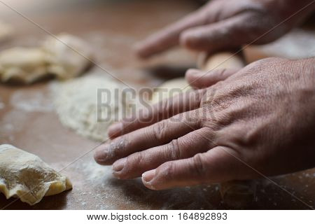 Old man rolls the dough raw hands. Man prepares the dough for the preparation of pasta on a wooden table. Handmade.