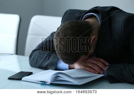 Businessman asleep at his desk in the office