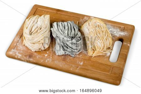 Top view on plane with raw homemade pasta with flour and vintage rolling pin over old wooden table. See series