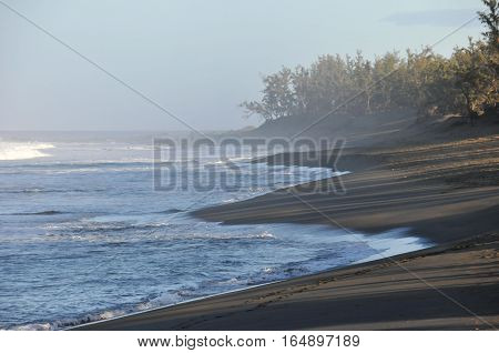 Beach with Dark Sand and Blue Sea of The Reunion Island in the Morning Light with haze