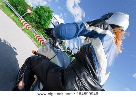 rear view of a woman riding her motorcycle, motion blur on ground, wheels and some of the background.