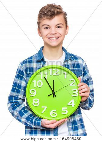 Portrait of caucasian teen boy with clock. Funny teenager showing green clock, looking at camera. Child back to school, isolated on white. Education and time concept or last minute christmas holiday.