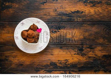 Valentine day white vintage plates sweets and hearts made from red paper and grated chocolate. Top view flat lay wooden rustic table.