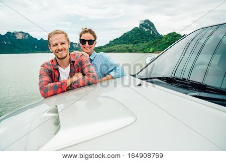 young couple traveling by car. portrait of a man and woman embracing and looking at camera on the background of mountain scenery of the lake and sky. romantic vacation and travel.