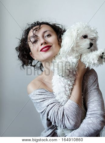Portrait of the young pretty brunette woman with curly hair and wine lips color holding on her hands puppy white maltese dog.