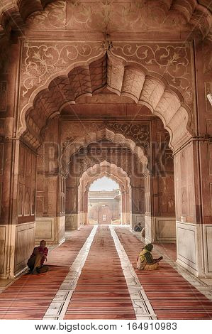 DELHI, INDIA - NOVEMBER 20, 2016: The Jama Masjid is the largest mosque in Delhi, India. It was built in the 17th century by the Mughal Emperors and the Islamic influence is still visible in the arches in the interior where people are praying.