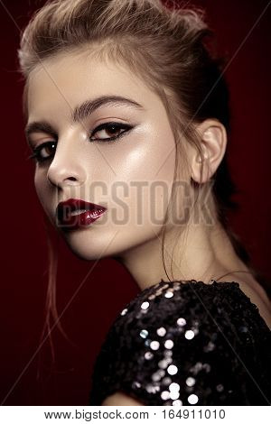 Bright beauty portrait of attractive female model with bright red lips on a red background.