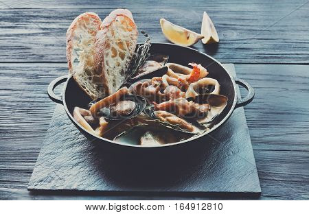 Seafood Stew in Saucepan. Authentic italian restaurant cuisine, healthy delicatessen food. Oysters, shrimps, calamari in white cream sauce with bruschetta. Bowl on dark blue wood background