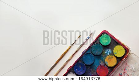 Water color pallet with two paint brushes next to it with a white background