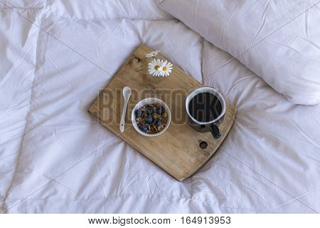 Breakfast in bed with coffee cereals and cranberries