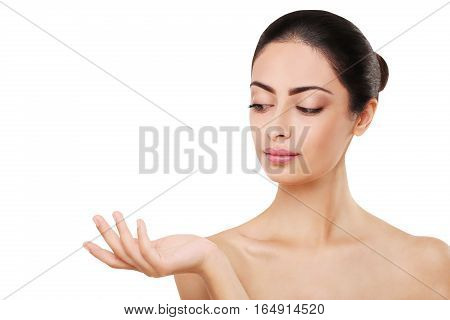 Beautiful indian girl with perfect skin and makeup. Beauty and health care concept. Ideal face of brunette, isolated on white background with copy space and hand holding or showing something