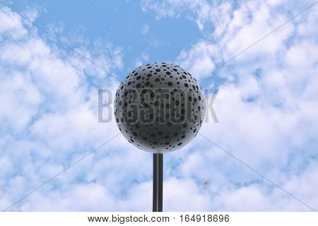 Abstract background. Metallic sphere against a blue sky. Empty copy space for editor's text.