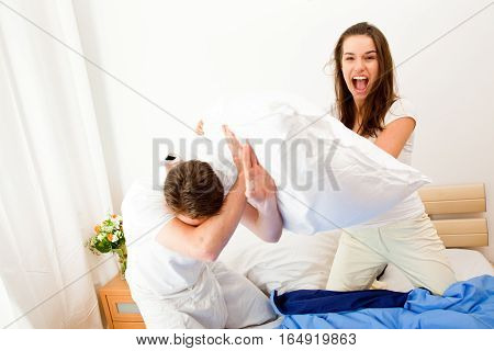 couple having a pillow fight in their bed.