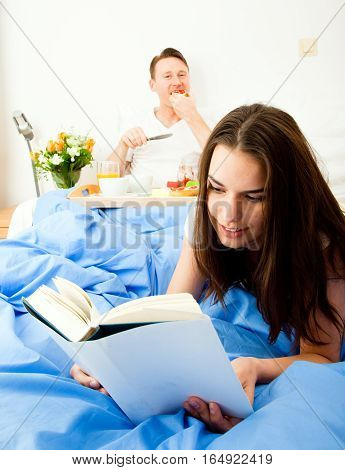 couple having breakfast in bed and reading a book