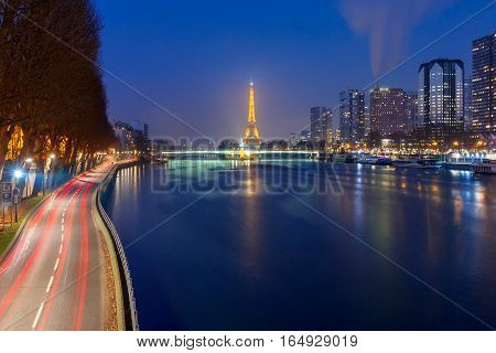 Paris, France - December 29, 2016: Panoramic Paris cityscape with Eiffel tower, quay de Grenelle and its reflection in the river Seine at night, as seen from bridge Pont Mirabeau, France
