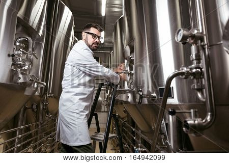 Magnificent worker. Glad young handsome man using brewing mechanism while spending time at factory and making beer.