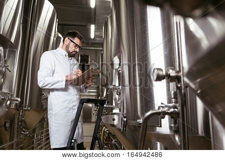 Be professional. Delighted young handsome man using ladder and brewing mechanism while working at factory and making beer.
