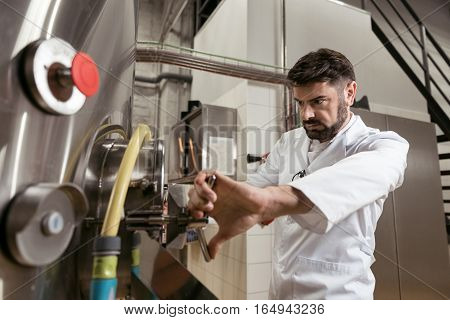 Hard work. Serious handsome young man opening the tap while working at beer factory and making product.