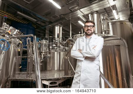 Delighted about work. Joyful handsome young man posing with brewing mechanisms notes while spending time at beer factory and working.
