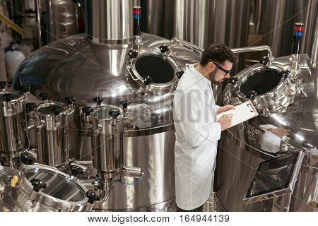 Serious and delighted. Concentrated young glad man controlling mechanisms while working at beer factory and making notes.