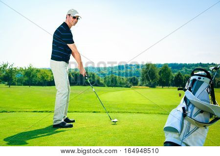 man teeing off on a golf course