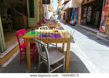 Rethymnon, Island Crete, Greece - June 23, 2016: Tables and chairs of cafe are on the narrow street of Rethymnon (part of Old Town)