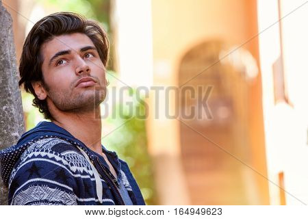 Young dreamer man thinking. A beautiful young man is looking up. Leaning against the wall. Good looks and fresh beauty.