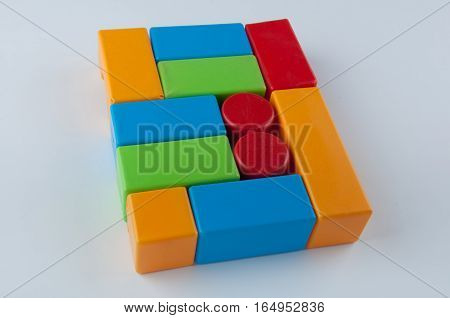 Child's toys. Red blue green yellow building blocks lay on white background in the form of rectangle