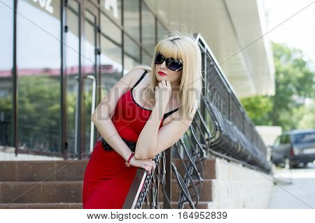 the woman looks from office leaning against hand-rail