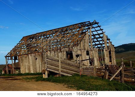 A deteriorating old barn in rural Eastern Oregon on a spring evening on a hill with very little of the roof left and a large portion of the wooden walls gone.