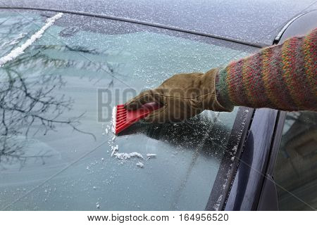 Winter scene human hand in glove scraping ice from windshield of car
