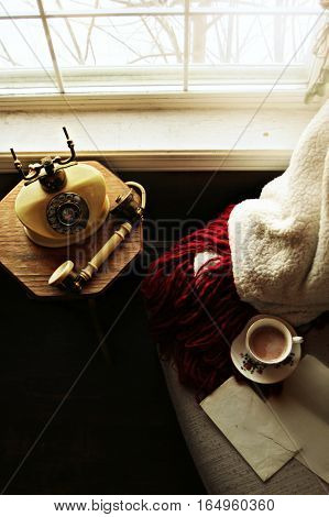 Cozy blanket and teacup on chair with vintage telephone on wooden table by the window.