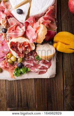Jamon. Brie cheese. Antipasti and fruit concept. Tasting gourmet party on a rustic wooden table. A quick and easy snack for party time. Rustic style. Antipasti platter with different meat and cheese
