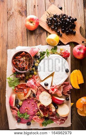 Cold meat plate and bread on wooden background.Antipasto Platter Cold meat plate with baguette. Delicatessen Cold Cuts with Ham Pepperoni Salami Finocchiona Olives Camembert. Jamon. Brie cheese.
