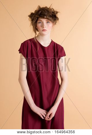 Portrait of red-haired woman with freckles in a burgundy dress on beige background. Fashion model. Woman with perfect skin. Woman wi with nude makeup. Fashion photography concept