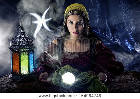 Psychic or fortune teller with crystal ball and horoscope zodiac sign of Pisces