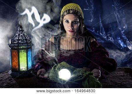 Psychic or fortune teller with crystal ball and horoscope zodiac sign of capricorn