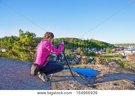 Woman with a photocamera early in the morning on a mount in Sandefjord. Norway