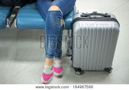 Young woman at international airport waiting for her flight. Female passenger at terminal indoors.