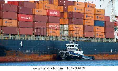 Oakland CA - January 01 2017: Tugboat Z-FIVE off the port side of cargo ship SEASPAN FELIXSTOWE assisting the vessel to maneuver into the Port of Oakland.