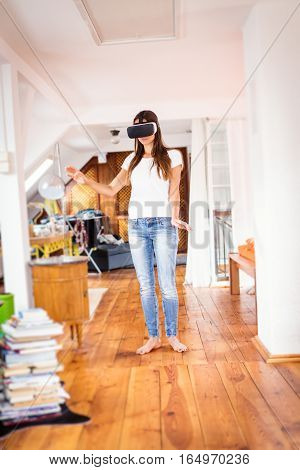 Young woman in her apartment, using VR glasses to watch a 3D movie.